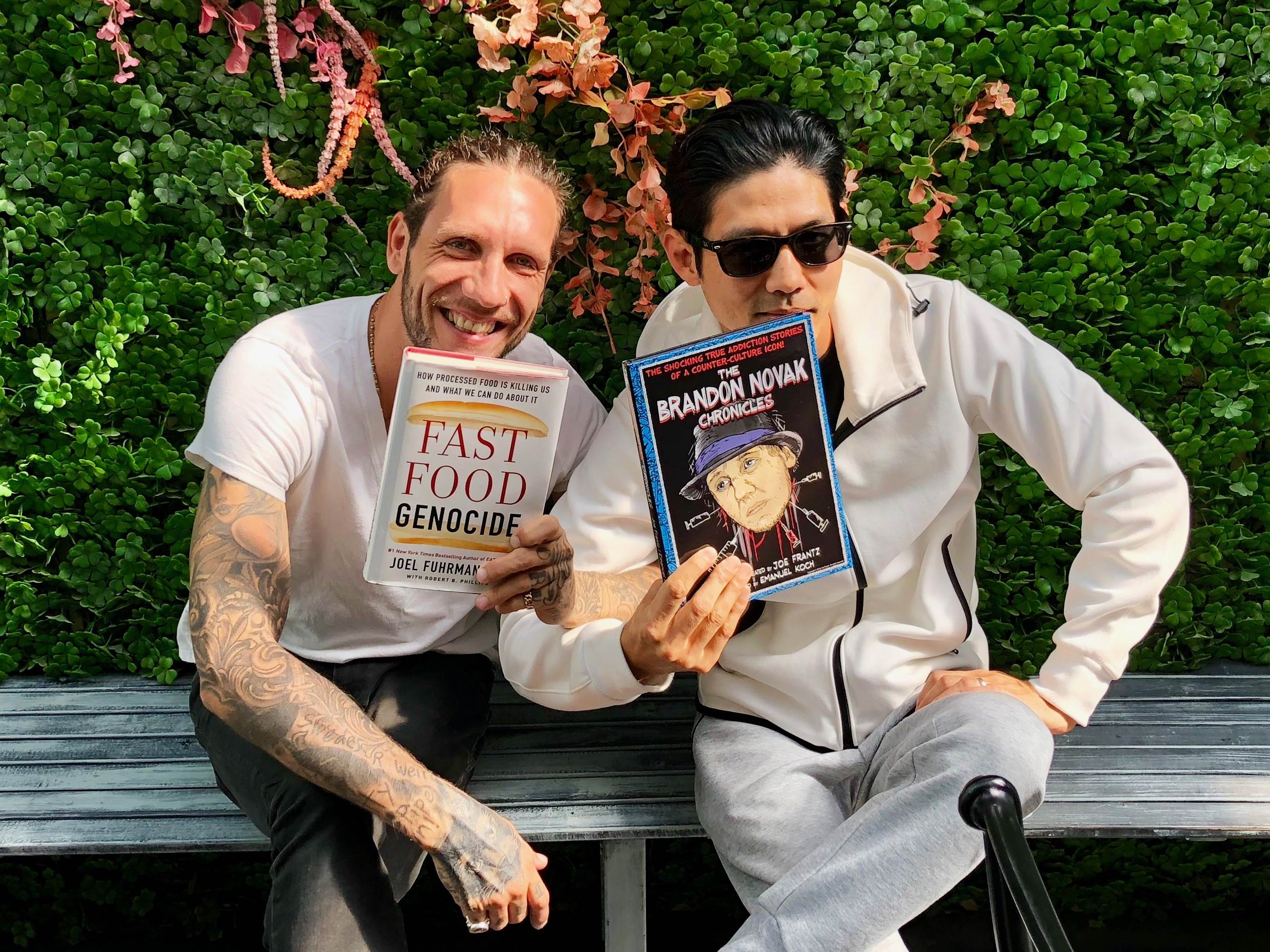 Brandon Novak and Dr Yi enjoying their new favorite books - Fast Food Genocide from fellow New York Times Best Selling Author Joel Fuhrman, MD and The Brandon Novak Chronicles